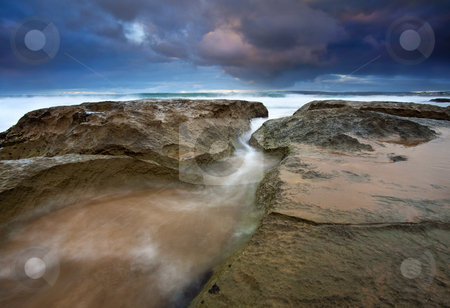 Storm Surge stock photo, A stormy sunrise at Knights Beach has the waves surging through every crack in the limestone. by Mike Dawson