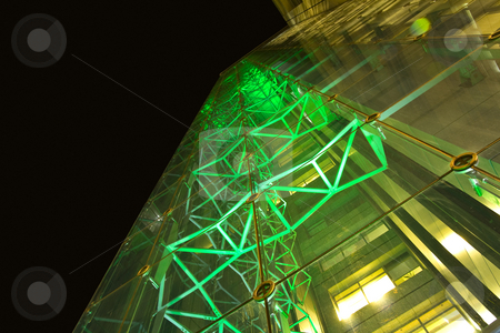 Office building at night with glass walls illuminated with green stock photo, A facade of office building shot at wide angle. hi-tech style metal construction is seen through the glass, illuminated with green light by Elizaveta Geshiktor