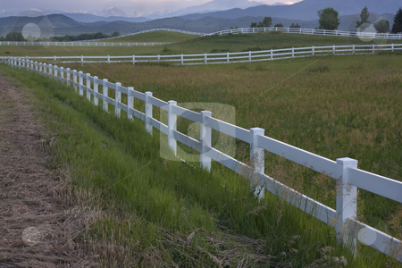 Dusk at pasture in Colorado foothills stock photo, Green horse pasture with white fences at foothills of Rocky Mountains in norhtern Colorado at dusk by Marek Uliasz