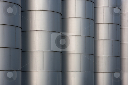 Grain bins - industrial background stock photo, A row of metal round grain storage bins with rivets - industrial background and texture by Marek Uliasz