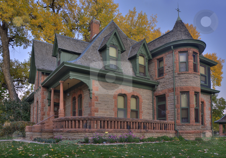 Historical sandstone house in Colorado stock photo, Avery house - historical landmark of Fort Collins, Colorado, at dawn against fall cottonwood foliage by Marek Uliasz