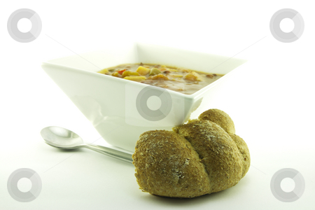 Soup in a White Bowl stock photo, Hot chunky vegetable soup in a small square white bowl with a bread bun and a spoon on a white background by Keith Wilson