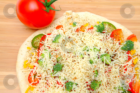 Vegtable Pizza For One stock photo, A veggie pizza ready to go into the oven topped with sharp cheddar and asiago cheese, fresh tomatoes, red bell pepper, mild jalapeno chilie, broccoli and dried herbs by Lynn Bendickson