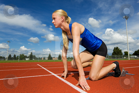 Ready to race stock photo, A teen athlete ready to race in the starting blocks by Steve Mcsweeny