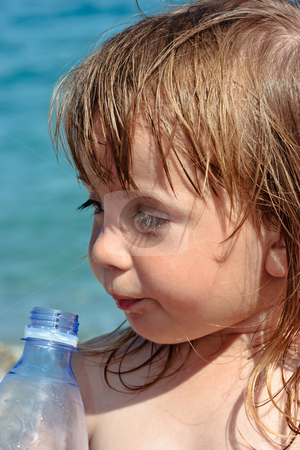 Thirsty girl stock photo, Little girl drinking from a bottle on a beach by Natalia Macheda