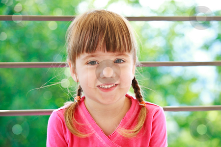 Little girl with two plaits stock photo, Little smiling girl with two plaits and pink t-shirt on a green background lookind directly in camera by Natalia Macheda