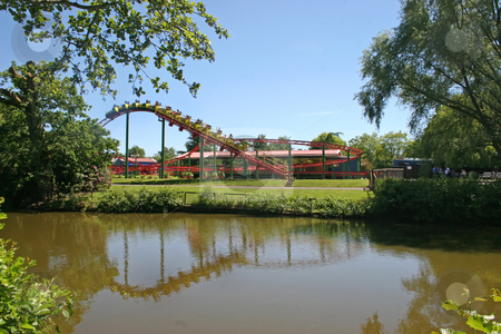 Amusement Ride stock photo, An attraction in a theme park with it's reflection in a lake. by Lucy Clark