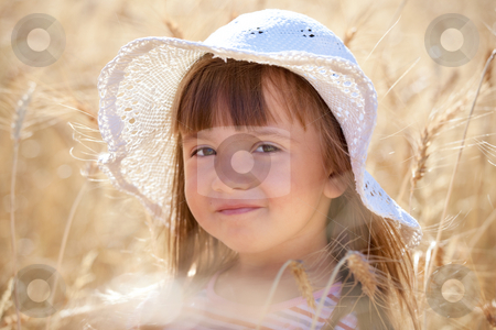 Lovely girl among wheat ears  stock photo, Lovely little girl with white hat among ripe wheat ears by Natalia Macheda