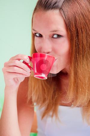 Redhead woman drinking coffee stock photo, Redhead young woman drinking coffee from red cup by Natalia Macheda
