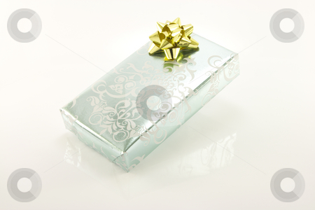 Silver Wrapped Gift stock photo, Single shiny silver wrapped gift with a gold bow on a reflective white background by Keith Wilson