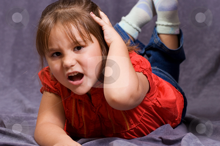 Hurt Head stock photo, A four year old girl holding her head in pain by Richard Nelson