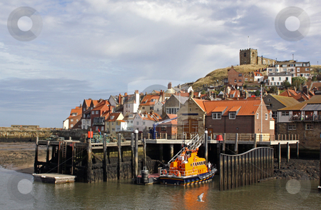 Whitby harbor and lifeboat stock photo, Scenic view of Whitby town harbor with lifeboat in foreground and church on hillside, North Yorkshire, England. by Martin Crowdy
