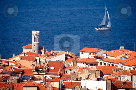 Piran, Slovenia stock photo, Roofs of a typical Southern European  town and a sailing boat by Interlight