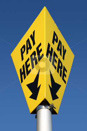 Yellow pay here car parking sign and blue sky. stock photo, Yellow pay here car parking sign and blue sky. by Stephen Rees