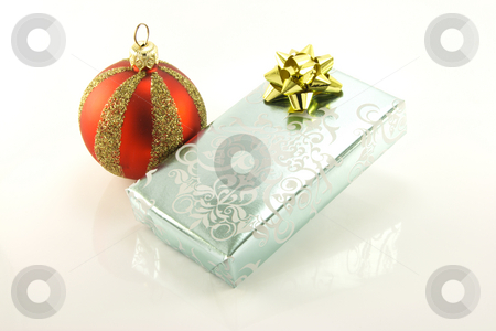 Silver Gift and Bauble stock photo, Single shiny silver wrapped gift with a red and gold bauble on a reflective white background by Keith Wilson