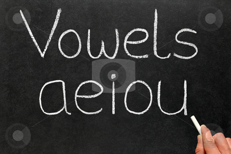 A teacher writing the five vowels letters on a blackboard. stock photo, A teacher writing the five vowels letters on a blackboard. by Stephen Rees