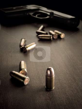 Bullets and handgun stock photo, bullets with handgun in the back of the scene with focus on the bullet,sepia toned, closeup with vignette, useful for various security,protection or criminal topics by Vladimir Koletic