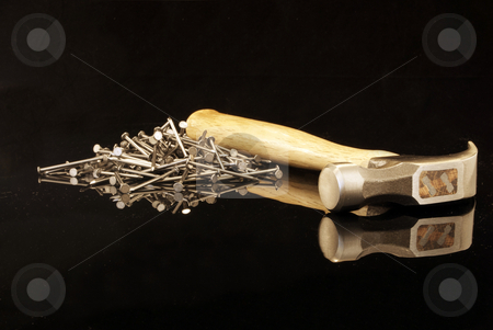 Hammer and Nails on Reflection stock photo, Royalty free stock image of a hammer with nails isolated on black and on a black reflective surface with copy space provided by Paul Inkles