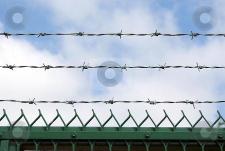 Barbs! stock photo, Royalty Free Stock Image of three rows of barbed wire against cloudy blue sky by Paul Inkles