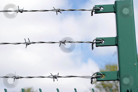 Barbed Wire stock photo, Royalty Free Stock Image of three rows of barbed wire against cloudy blue sky with post to right, copyspace provided by Paul Inkles