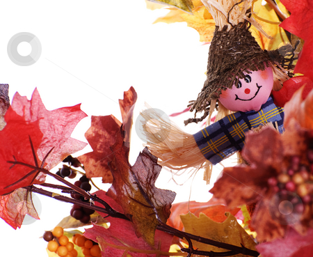 Small Scarecrow stock photo, A small scarecrow peaking behind some artificial fall leaves, isolated against a white background by Richard Nelson