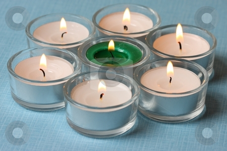 Seven tea lights stock photo, Seven tea lights on light blue background by Arnold Barna