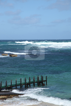 Pier choppy seas stock photo, Wooden pier on beach with choppy blue seas by Kheng Guan Toh