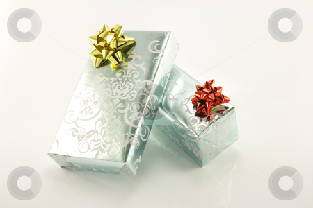 Two Silver Wrapped Gifts stock photo, Two shiny silver wrapped gifts on a reflective white background by Keith Wilson