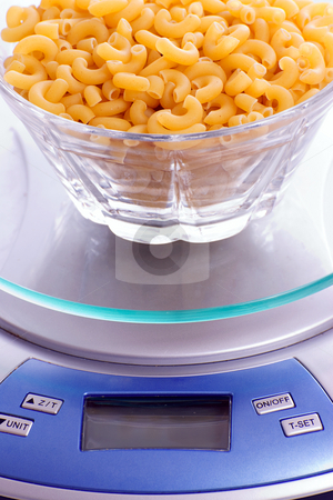 Macaroni Noodles Being Weighed stock photo, A bowl of uncooked macaroni full of carbohydrates, sitting on a food scale by Richard Nelson