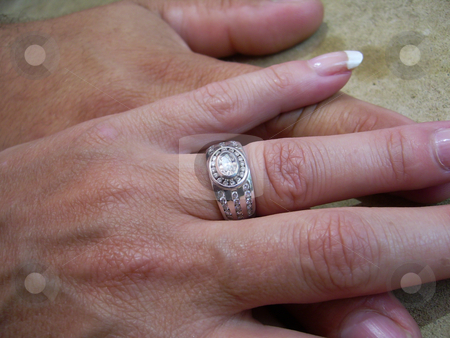 Loving Hands stock photo, Two hands on a cement like background on top of each other showing woman's beautiful wedding ring by Ian Genis