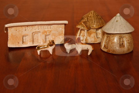 African Homes stock photo, A set of clay African houses with clay cattle on a wood  background by Ian Genis