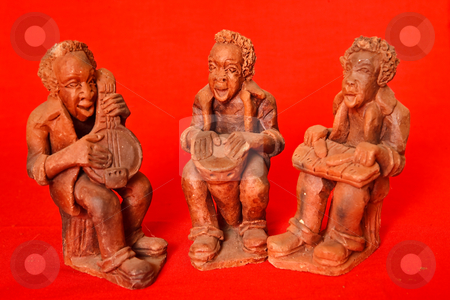 African Trio stock photo, A trio 8of clay hand made African musicians on a red background by Ian Genis