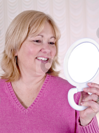 Mature Woman looking in mirror stock photo, Mature Woman by Jim DeLillo