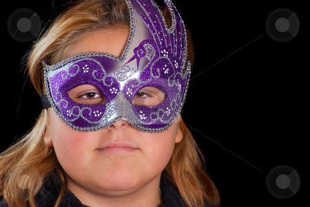 Costume Party stock photo, Closeup of a young blonde girl wearing a venetian mask, shot against a black background by Richard Nelson