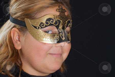 Venetian Mask stock photo, Closeup of a young blonde girl wearing a venetian mask, shot against a black background by Richard Nelson