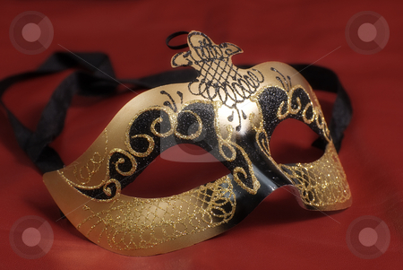 Golden Mask stock photo, Closeup of a venetian mask commonly used in theatrical plays shot on red by Richard Nelson