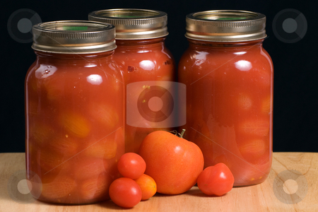 Jars of Tomatoes stock photo, Three mason jars filled with canned tomatoes shot on a wooden board and isolated against a black background by Richard Nelson