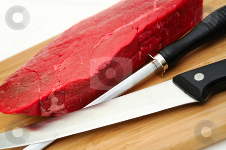 Raw Steak An Knife stock photo, A large uncooked steak on a cutting board with butcher knife and sharpener on a white background by Lynn Bendickson