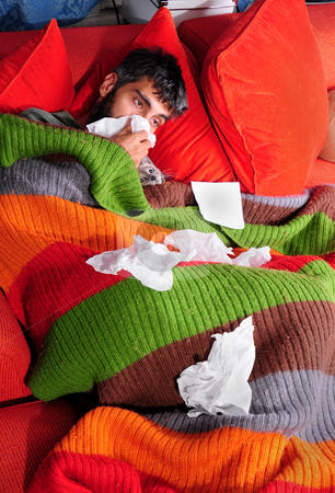 At Home with the Flu and Kitty stock photo, A man at home with the flu. He's wrapped up in a blanket on the couch with his cat and tissue paper. by Mehmet ali Ertek