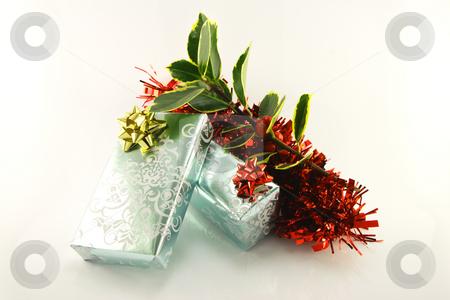Gifts and Holly stock photo, Two silver shiny gifts with red and gold bows, a sprig of holly and red tinsel on a reflective white background by Keith Wilson