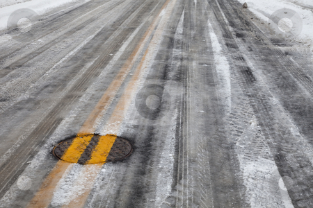 Slippery icy road with yellow line stock photo, Street asphalt pavement covered by snow and ice, double yellow line across manhole cover by Marek Uliasz