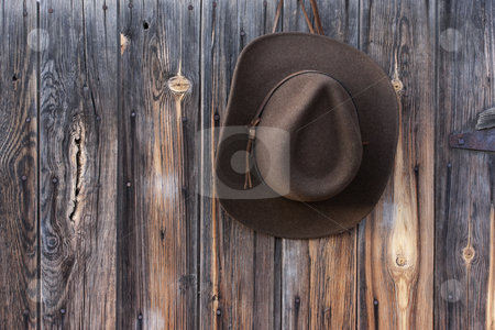 Felt cowboy hat on barn wall  stock photo, Brown wool felt cowboy hat with leather headband hanging on weathered wooden wall of old barn by Marek Uliasz