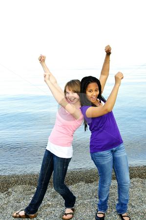 Happy girlfriends stock photo, Portrait of two teenage girl friends raising arms by Elena Elisseeva