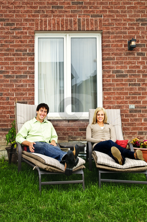 Happy couple relaxing at home stock photo, Happy couple in backyard of new home sitting on lounge chairs by Elena Elisseeva