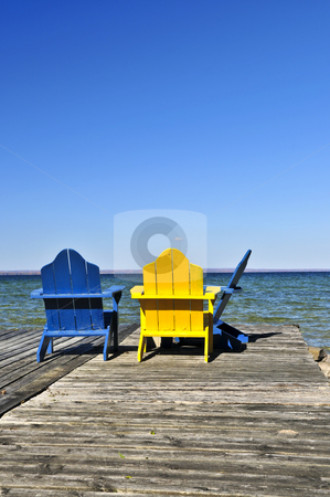 Chairs on wooden dock at lake stock photo, Painted wooden chairs on dock at a lake by Elena Elisseeva