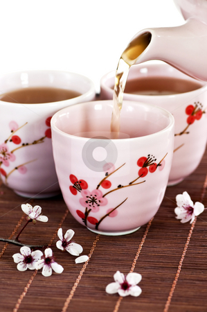 Pouring green tea stock photo, Pouring green tea into cups with cherry blossom design by Elena Elisseeva