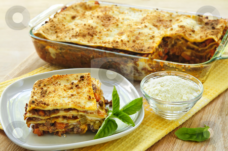 Lasagna stock photo, Fresh baked lasagna casserole with a serving cut by Elena Elisseeva