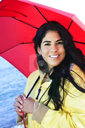 Beautiful young woman in raincoat with umbrella stock photo, Portrait of beautiful smiling brunette girl wearing yellow raincoat holding red umbrella by Elena Elisseeva