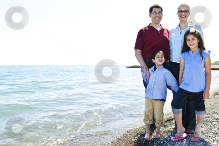 Happy family at beach stock photo, Happy family standing on shore at the beach by Elena Elisseeva