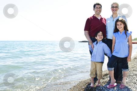 Happy family at beach stock photo, Happy family standing on shore at the beach by Elena Elisseeva